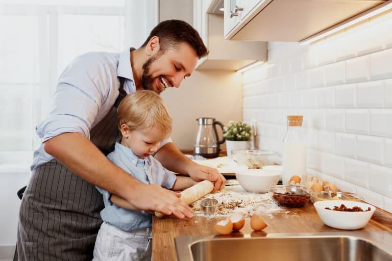 Lachender Vater, welcher mit seinem Sohn Kekse macht.