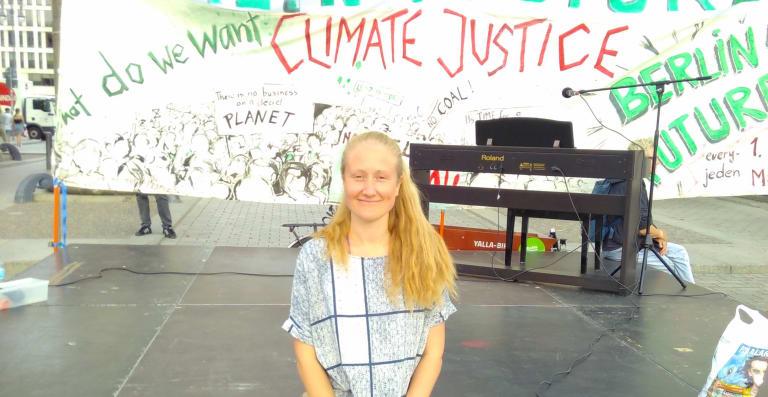 Jenny auf der Bühne auf einer Demo mit einem 'Climate Justice' Banner im Hintergrund