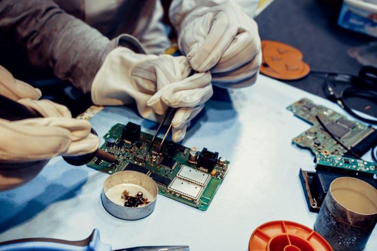 Zwei Personen mit Handschuhen, welche eine Platine reparieren.