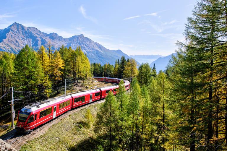 Ein Zug fährt durch eine hügelige Landschaft