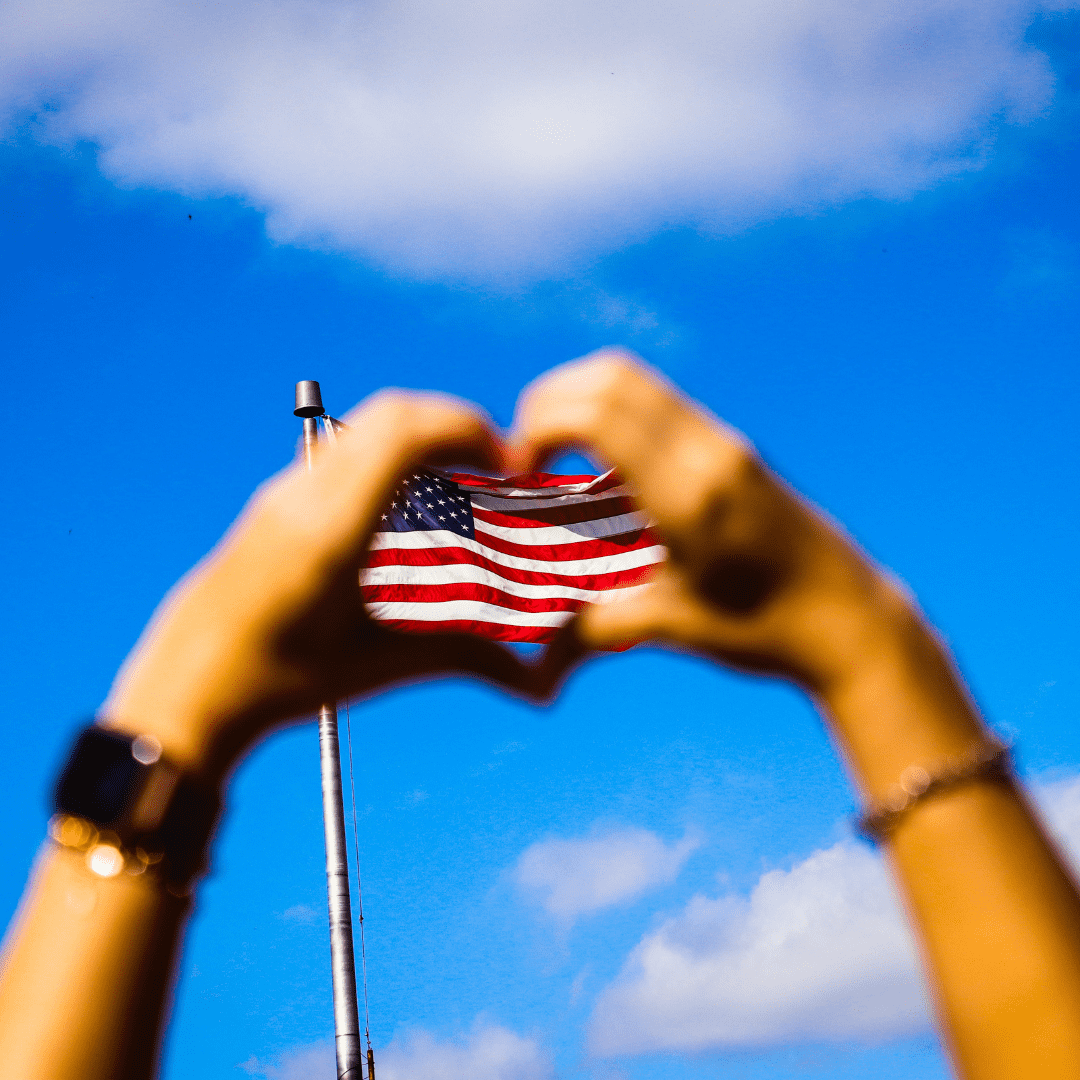 hands making heart shape with American flag in background against blue sky