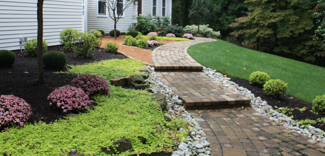 paver patio lined with manicured flowers and bushes