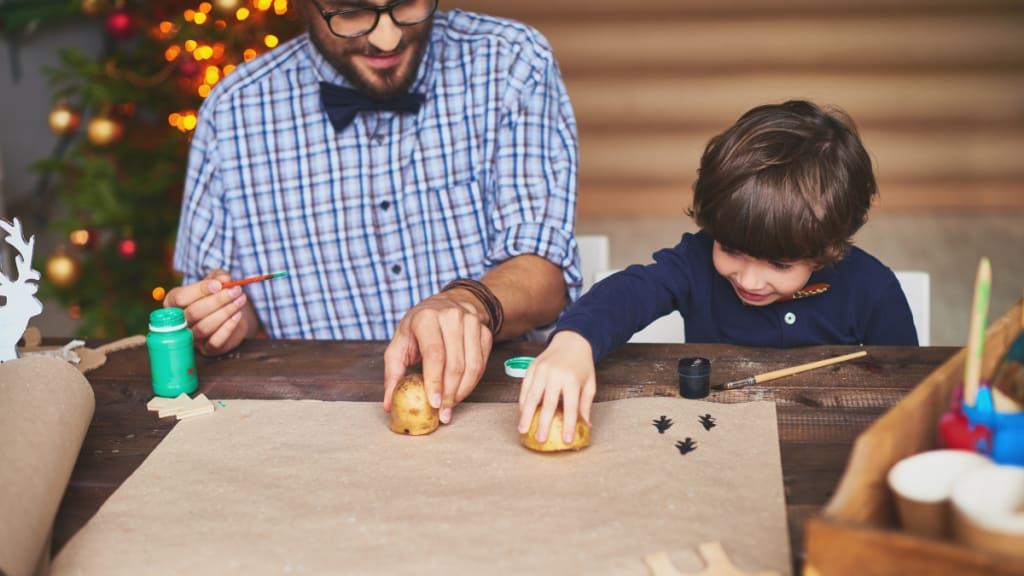 father and son creating customised wrapping paper with potato stamps
