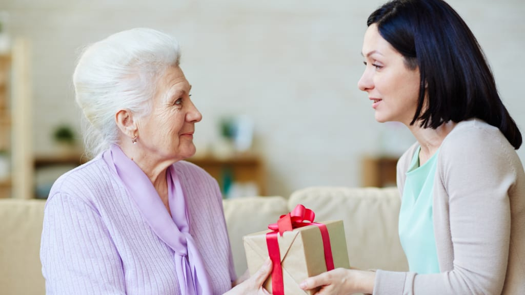 daughter giving mother a gift