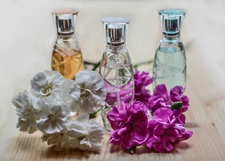 perfume bottles next to white and purple flowers