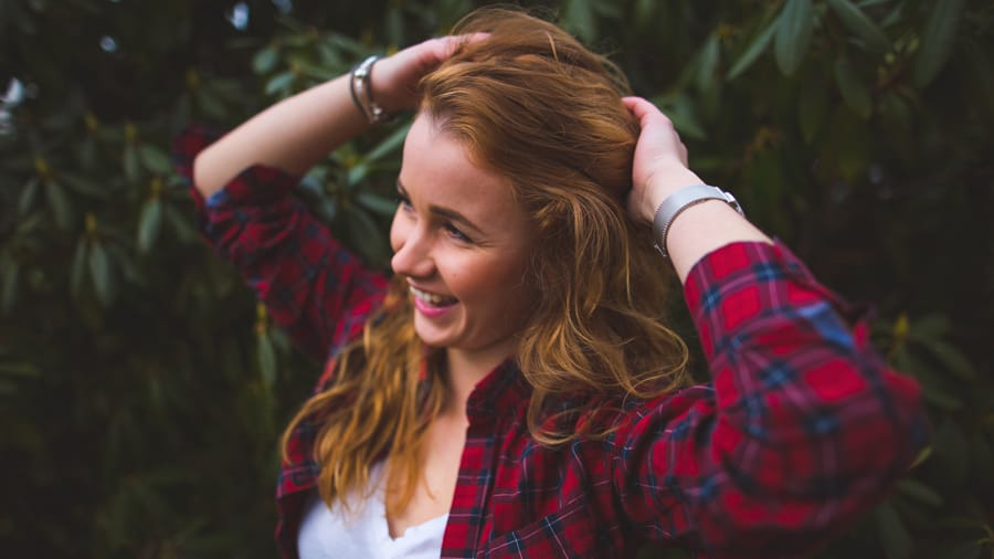 Beautiful dark blonde girl smiling wearing white v-neck shirt red plaid shirt​