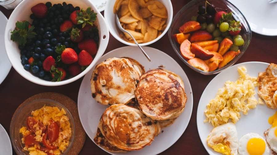 Different foods like eggs, muffins, strawberries, blackberries, tomatoes in separate plates on a white table