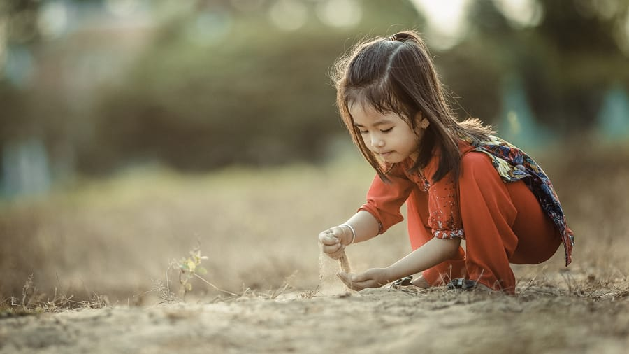 Vietnamese child in red outfit playing outdoors pouring sand through her fingers