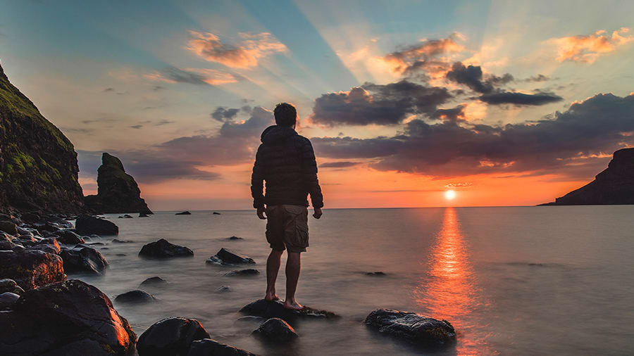 Man standing at seashore looking at sunset horizon