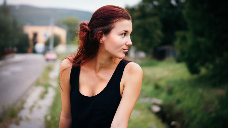 ​Petite woman with red hair loosely tied in a bun wearing a black tank top looking to her left