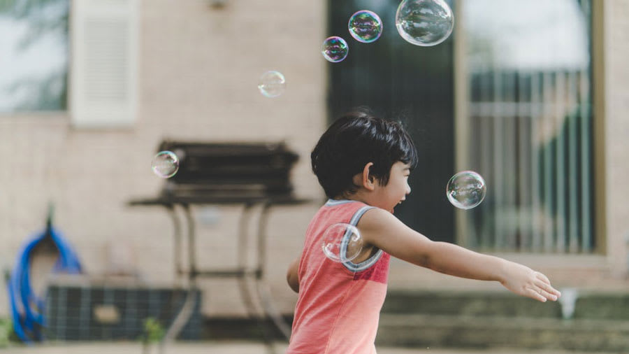 ​young boy child with short black hair wearing a red tank top running laughing playing in the street with bubbles