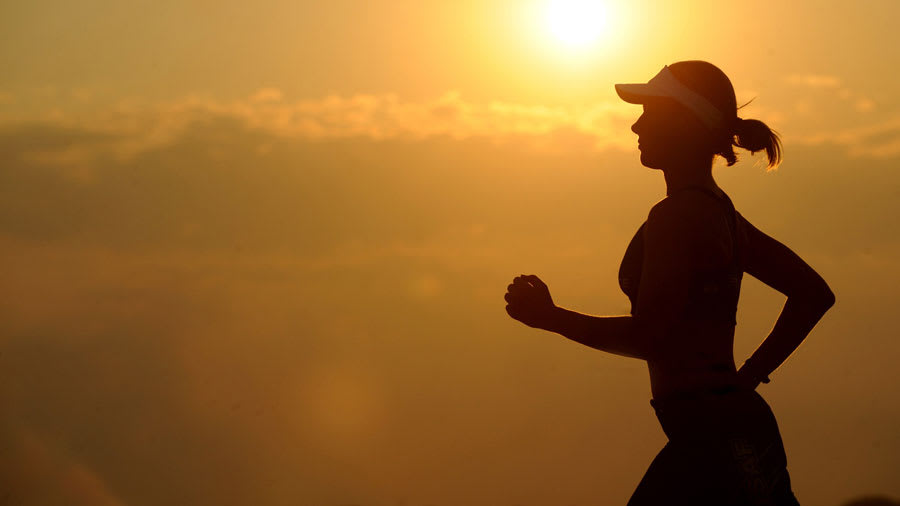 ​Woman Jogging Silhouette in Front of Bright Sun