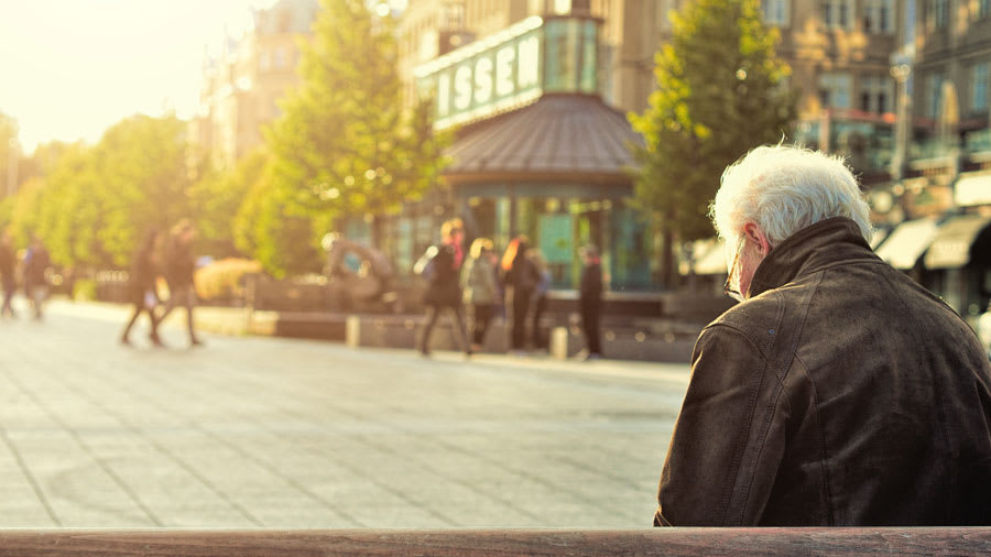 Old man with white hair wearing black leather jacket sitting on a park bench
