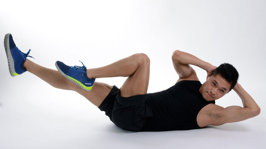 Man performing abdominal crunch exercises in black shirt and shorts