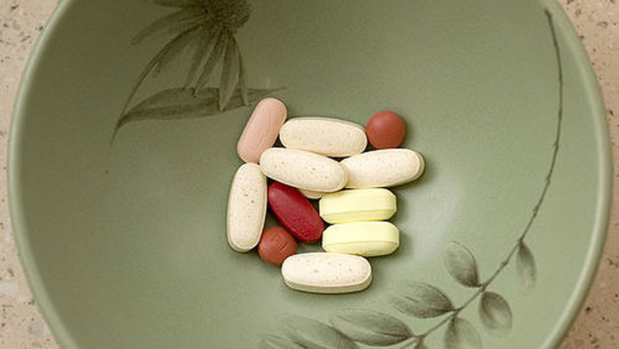 ​Pills placed in an olive green bowl decorated with flowers