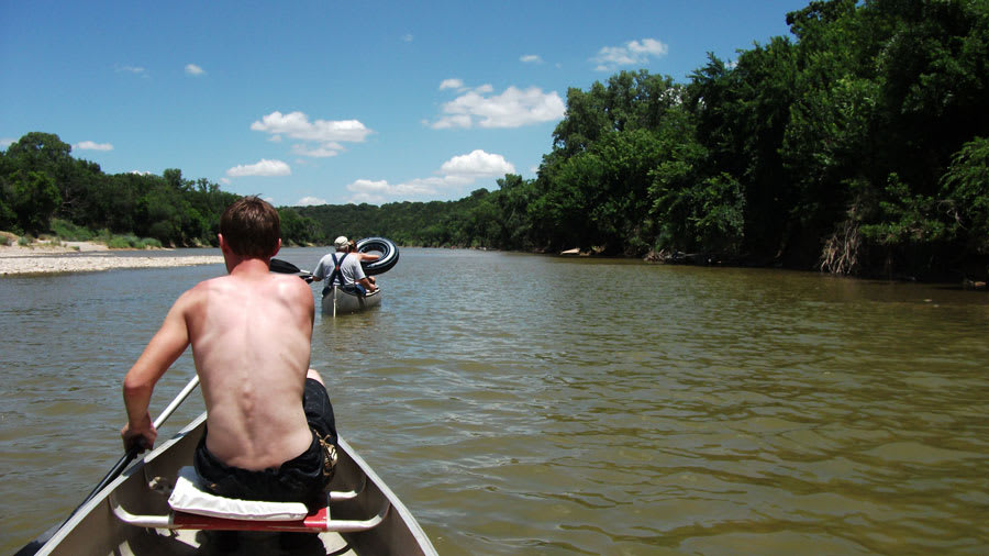 Man canoeing on river with sunburns on the shoulders