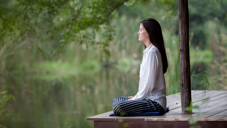 Woman with long black hair wearing striped pants and white button down shirt sitting cross-legged and meditating by a pond in Thailand