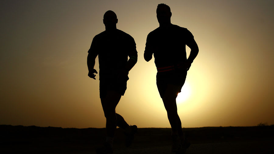 Two men jogging in silhoutte with sun