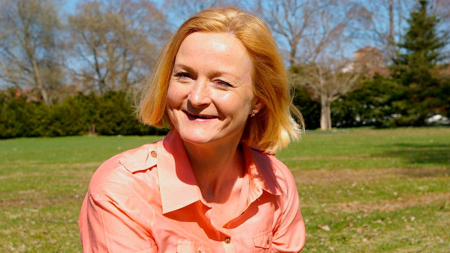 Middle aged Caucasian woman in pink collared shirt sitting at park with sun shining on face