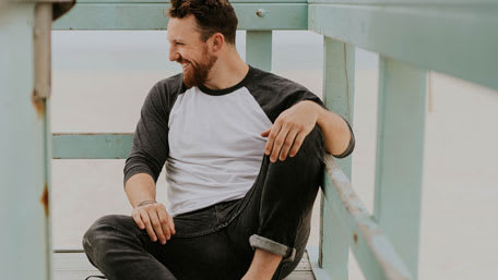 Man with beard smiling and looking right sitting on a deck with legs apart Credit: Brooke Cagle at Unsplash.com