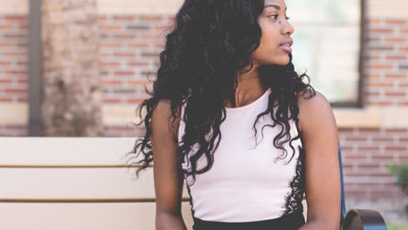 Beautiful black woman sitting on bench and looking left with beautiful long wavy hair Credit: William Stitt at Unsplash.com