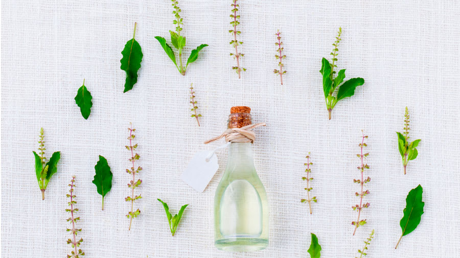 Aromatherapy essential oil in a bottle surrounded by leaves and flowers on a white canvas