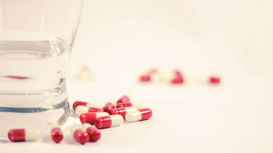 Red and white antibiotic pills and capsules next to a glass of water