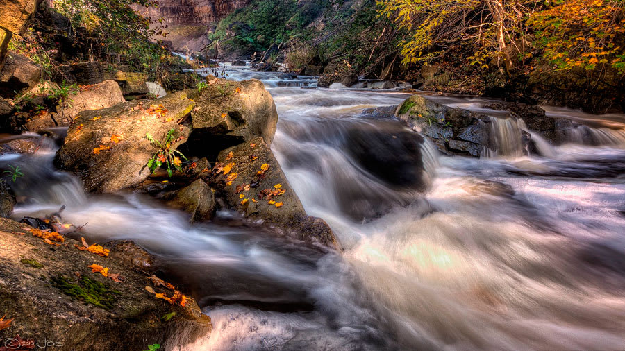 ​Stream water flowing over rocks with sunshine on one of the rocks