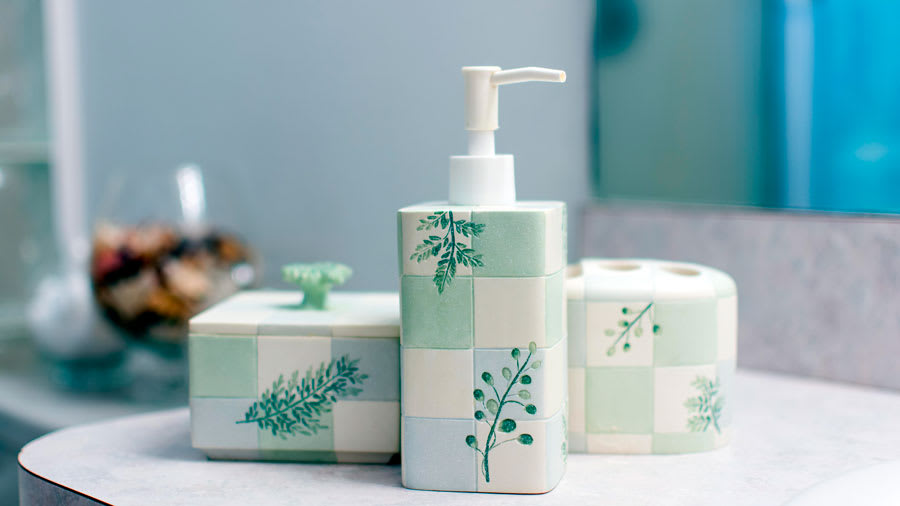 Pastel blue and green and white bathroom set on sink countertop