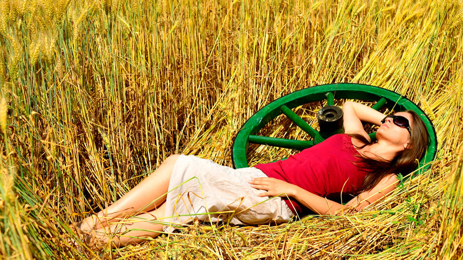 Woman laying on green wheel in hay with red shirt and beige skirt relaxing in sunlight with sunglasses