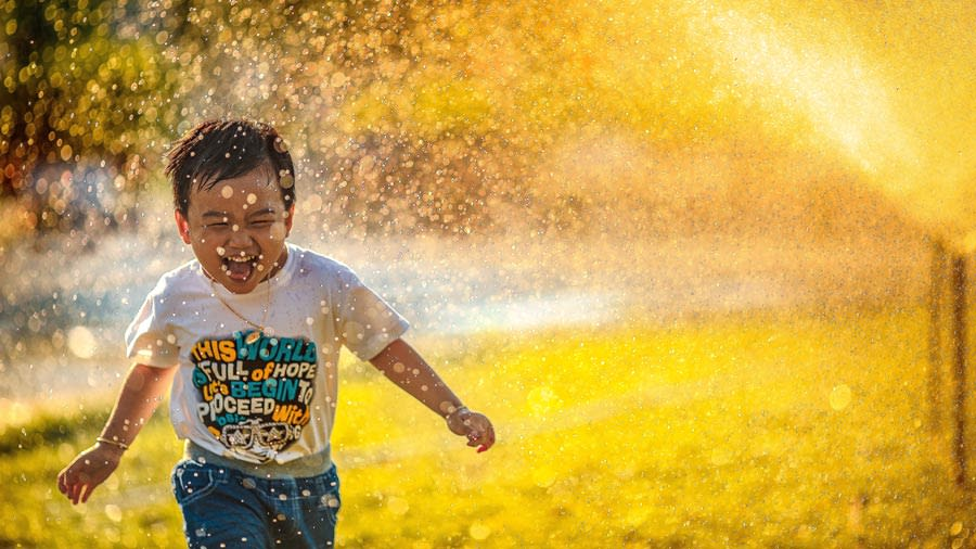 Boy running through sprinkler and laughing on a sunny day