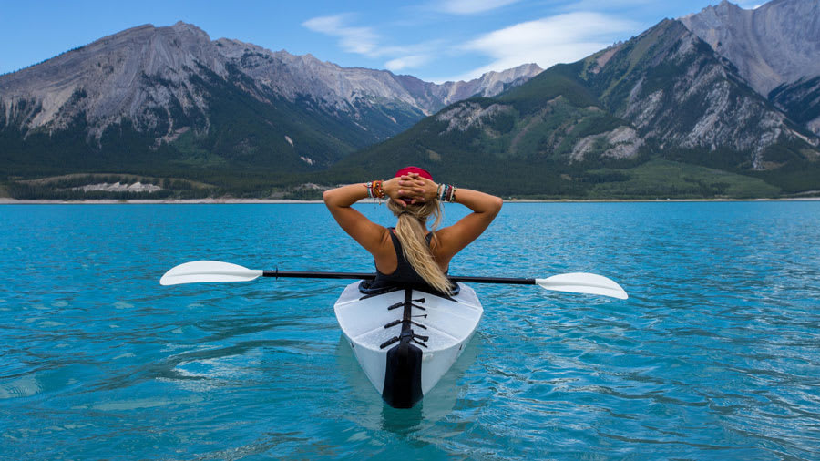 Woman exercising in a kayak to lower stress and improve her skin