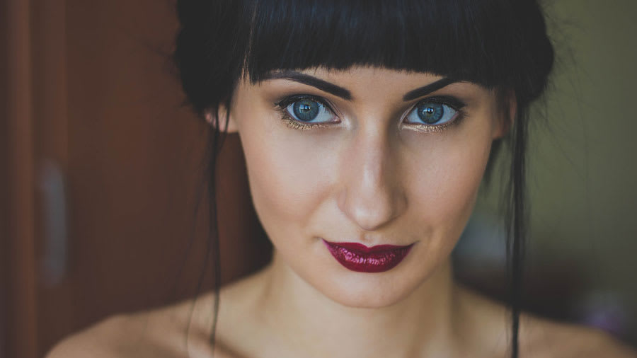 beautiful woman with dark red lipstick and colored eyes