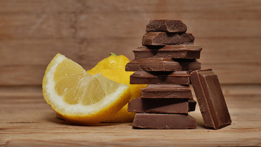 chocolate pieces stacked in balance next to slice of lemon