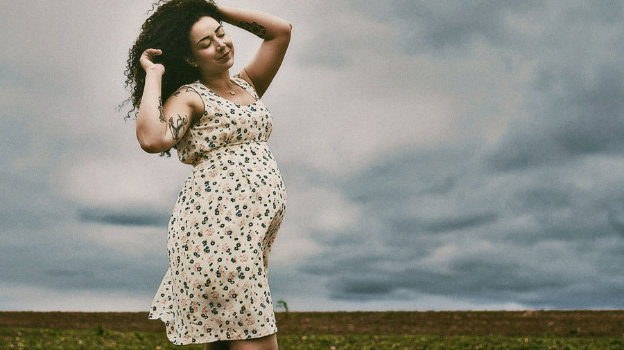 Pregnant woman with beautiful, glowing skin in an open field