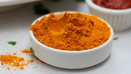 Turmeric in a white open container on the table with some spilled on the table
