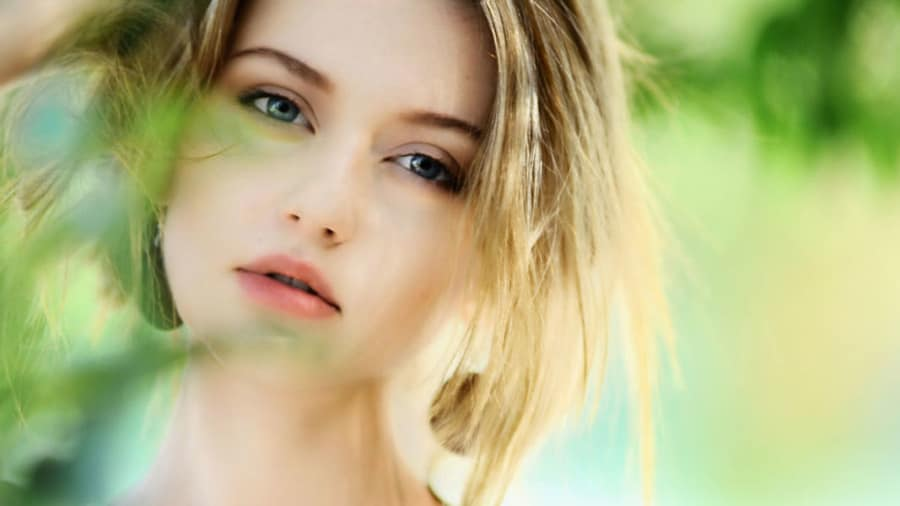 face of beautiful blonde woman with glowing skin and out-of-focus leaves in front of face