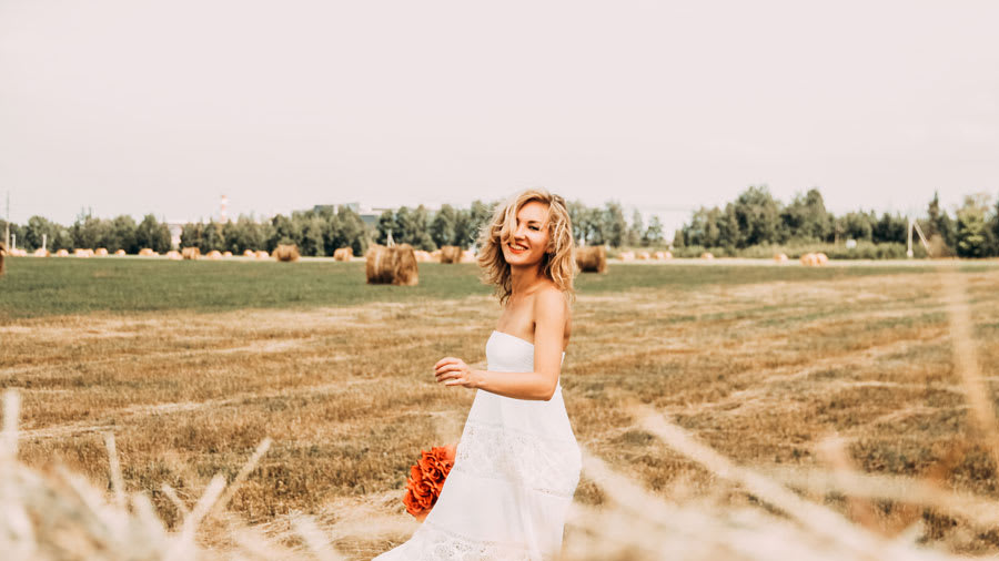 Woman in white dress standing outside in a field