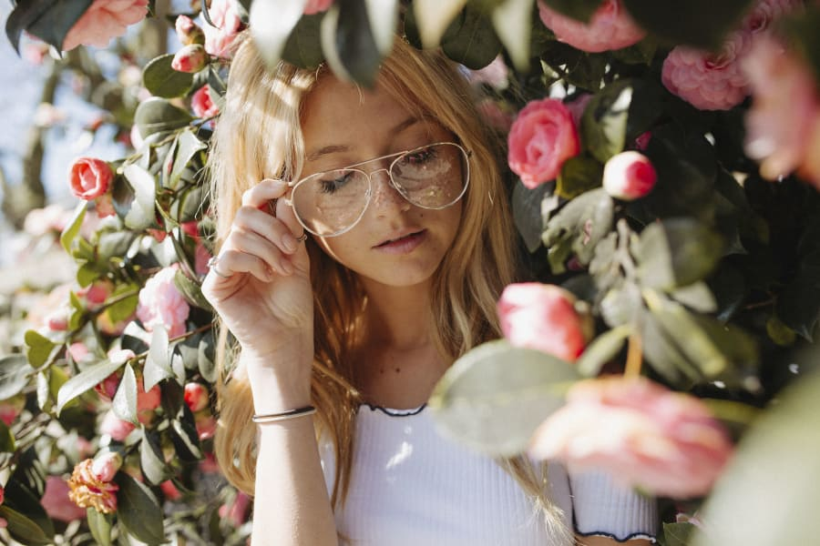 blonde haired girl with glasses looking at pink flowers