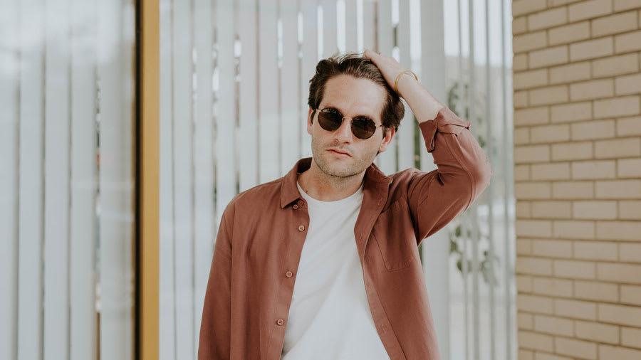 man wearing sunglasses scratching scalp psoriasis