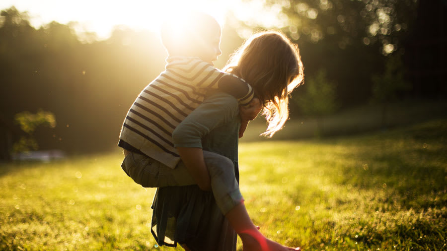 child getting piggyback ride on mother outside with sun shining on them.
