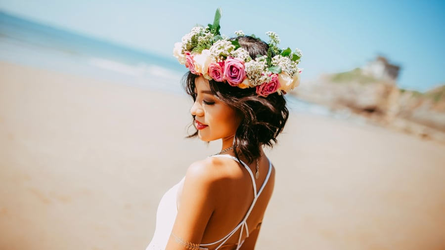 Girl on a beach wearing a flower hat