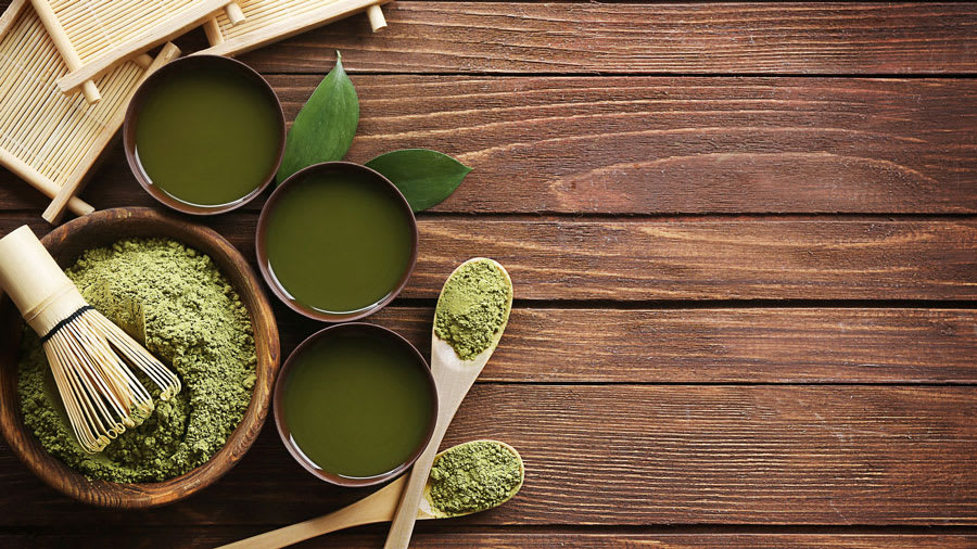 Spices and matcha green tea one a wooden table
