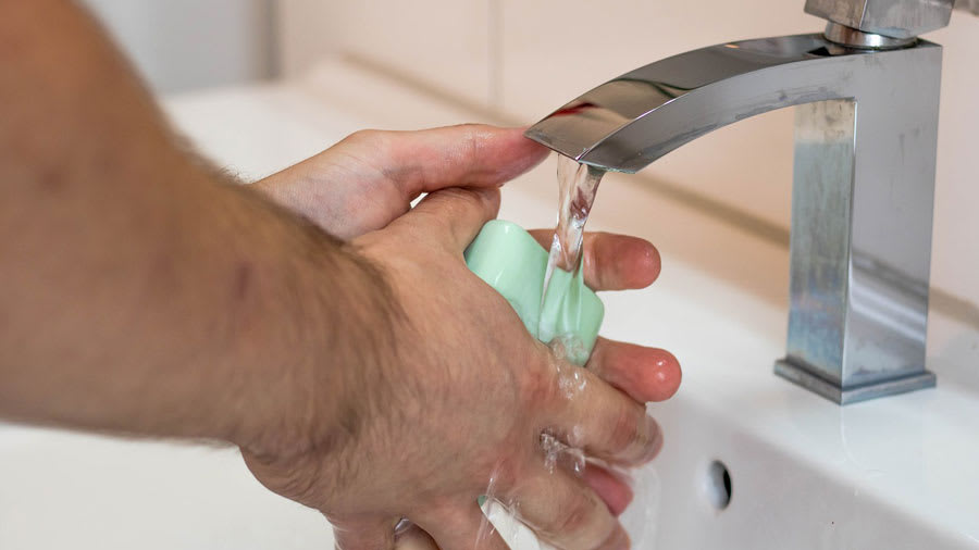 Hand washing with bar soap under the faucet to wash bacteria off hands
