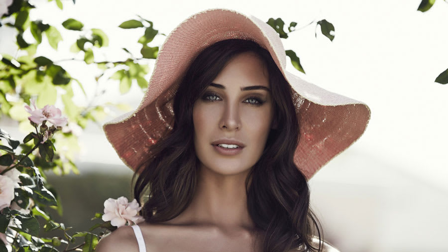 Beautiful woman in floppy hat outdoors with green plant behind her