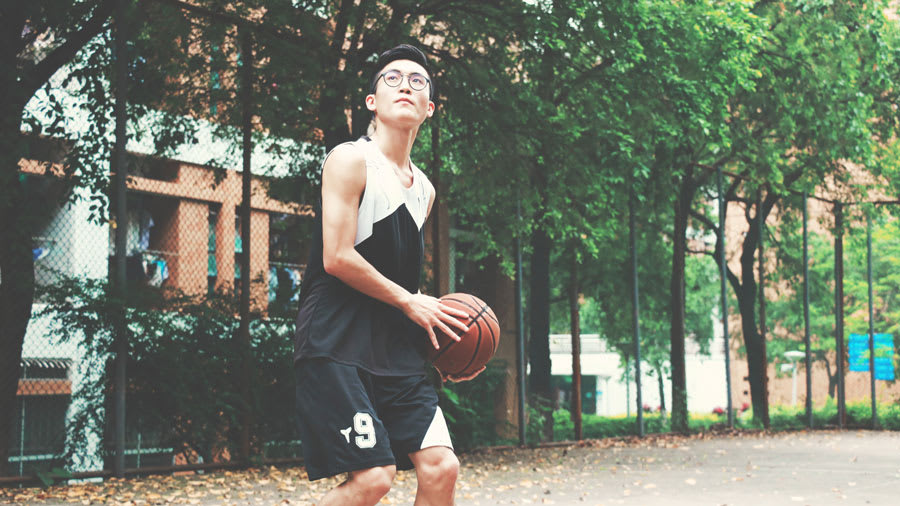 asian man playing basketball to exercise for psoriasis