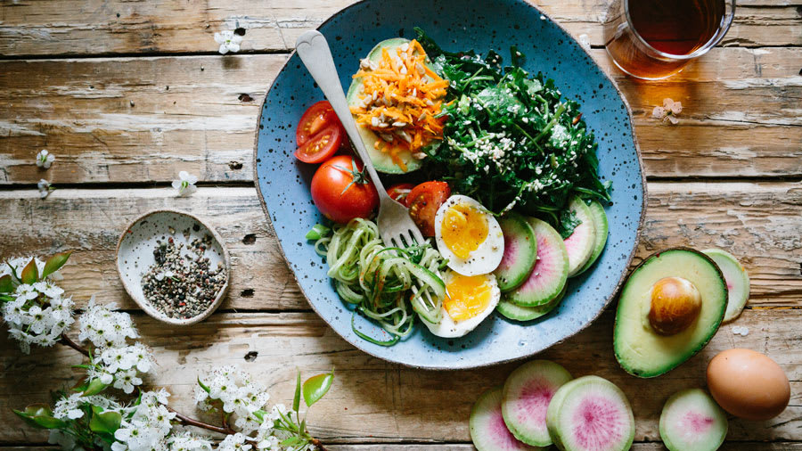 Blue bowl on wooden table with hard boiled egg, avocado, and other protein filled foods.
