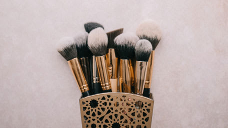 tapered makeup brushes in golden container