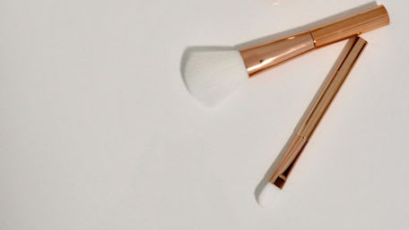 gold silicone makeup brushes against white background