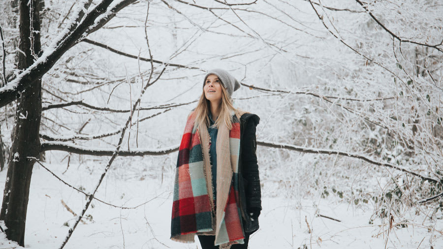 Blonde woman with color scarf standing outside exposing her skin to the winter snow